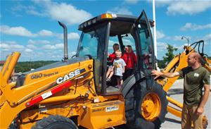 Kids climbing into backhoe at Pleasant Hill on Wheels